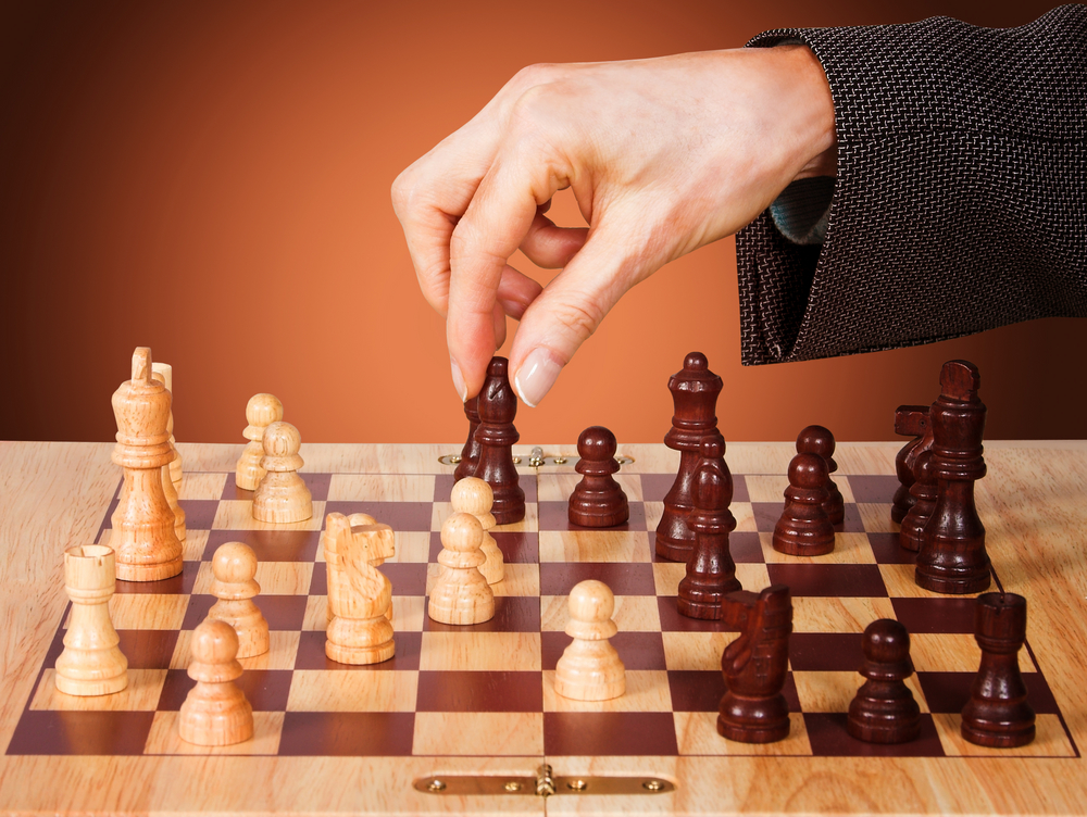 Business female hand moving a chess piece