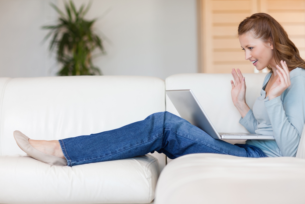 Excited young woman on the sofa waiting for online auction to be over