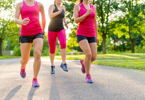 group of healthy girls running outdoors at sunset with lens flare.